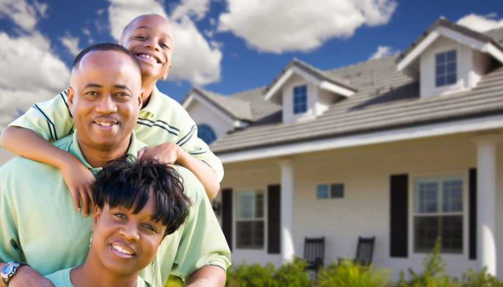 Attractive African American Family in Front of Beautiful House.